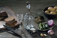 Vodka in un decantatore a cristallo e vari prodotti per gli spuntini Fotografia Stock