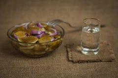 Vodka y un bocado de setas conservadas en vinagre en fondo marrón Imagen de archivo