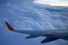 Voe aviões de passageiro em voo sobre as nuvens da noite Fotos de Stock
