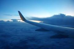 Voe aviões de passageiro em voo sobre as nuvens da noite Fotografia de Stock Royalty Free
