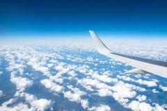 Voe a vista do avião no winglets e motor de jato, nuvens macias na skyline durante o nível de voo da escalada imagem de stock