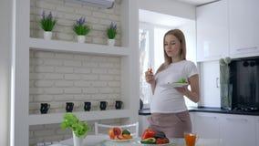 Voeding en dieet tijdens zwangerschap, vrouw met een plaat van salade in handen die paprika en liefkozingen binnen eten haar buik stock video