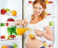 Voeding en dieet tijdens zwangerschap Zwangere vrouw met sinaasappel Royalty-vrije Stock Foto's