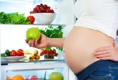 Voeding en dieet tijdens zwangerschap Zwangere vrouw met vruchten Royalty-vrije Stock Afbeelding