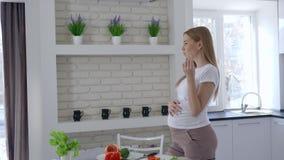 Voeding tijdens zwangerschap, mooie meisjes snijdende groenten en het eten van paprika's die haar grote buik in keuken houden stock videobeelden