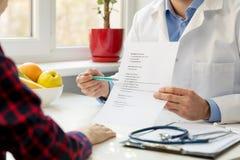 Voedingsdeskundige en patiënt die evenwichtig voedingsplan bespreken stock fotografie