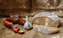 Voedsel: brood, wodka, knoflook en worst Stock Afbeelding