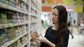 Voedsel, de puree en de sappen van de moeder denken het uitgezochte baby voor kind binnen van marktplaats en om te kopen De vrouw stock footage