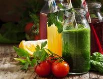 Voedsel en dranken, selectie van groente en vruchtensappen en smoothies in glasflessen met ingredi?nten dat, op rustieke houten w royalty-vrije stock afbeeldingen