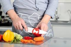 Voedsel, familie, het koken en mensenconcept - Mensen hakkende paprika op scherpe raad met mes in keuken Stock Foto
