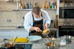 Voedsel het koken, beroep en mensenconcept - de mannelijke dienende plaat van de chef-kokkok van polenta en kalfsvleestongen met  stock foto's