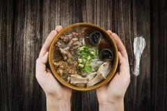 voedsel van de noedelvietnam van de holdingskom het Eigengemaakte, Traditionele Vietnamese soep en rijstebrij op een houten achte stock afbeeldingen