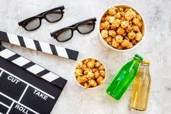 Voedsel voor het letten op film Popcorn en soda dichtbij clapperboard, glazen op grijze hoogste mening als achtergrond copyspace Stock Afbeeldingen