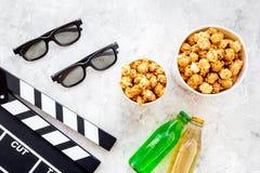 Voedsel voor het letten op film Popcorn en soda dichtbij clapperboard, glazen op grijze hoogste mening als achtergrond copyspace Stock Foto