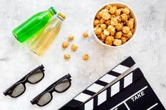 Voedsel voor het letten op film Popcorn en soda dichtbij clapperboard, glazen op grijze hoogste mening als achtergrond copyspace Stock Fotografie