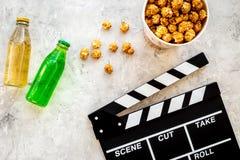 Voedsel voor het letten op film Popcorn en soda dichtbij clapperboard, glazen op grijze hoogste mening als achtergrond copyspace Stock Afbeelding