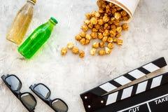 Voedsel voor het letten op film Popcorn en soda dichtbij clapperboard, glazen op grijze hoogste mening als achtergrond copyspace Royalty-vrije Stock Fotografie