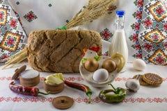 Voedselachtergrond met artisanaal brood, een fles melk, eieren, boter, zout, peper, knoflook, koekjes en tarweoren Royalty-vrije Stock Afbeelding