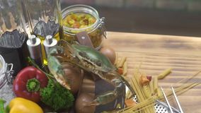 Voedselachtergrond met levende krab en verse groente in het Italiaans restaurant Leef krab binnen op ruwe plantaardige en droge d stock video