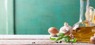 Voedselachtergrond met olijfolie, vers basilicum, deegwarentagliatelle, paddestoelen en peper op een houten achtergrond Stock Foto's