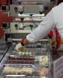Voedselarbeider gezet voedsel in plastic dienblad voor verpakking stock afbeelding