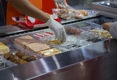 Voedselarbeider gezet voedsel in plastic dienblad voor verpakking royalty-vrije stock foto's