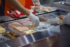 Voedselarbeider gezet voedsel in plastic dienblad voor verpakking royalty-vrije stock foto