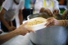 Voedselbehoeften van de armen in de maatschappijhulp met Voedselschenking: Het Concept Honger stock foto