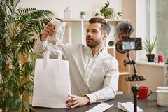 Voedselblog Jonge gebaarde blogger die een sandwich neemt terwijl het registreren van nieuwe video voor zijn Youtube-kanaal stock afbeelding