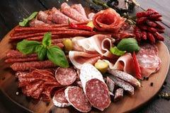 Voedseldienblad met heerlijke salami, stukken van gesneden prosciuttocrudo, worst en basilicum Vleesschotel met selectie royalty-vrije stock fotografie