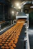 Voedselfabriek, productielijn of transportband met verse gebakken koekjes Moderne geautomatiseerde banketbakkerij en bakkerij stock afbeelding