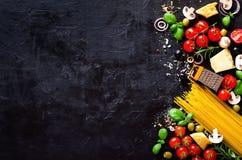 Voedselingrediënten voor Italiaanse deegwaren, spaghetti op de zwarte achtergrond van de steenlei exemplaarruimte van uw tekst Royalty-vrije Stock Foto