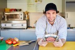 Voedselondernemer die tevreden met zijn vlees van de kwaliteitshamburger kijken Royalty-vrije Stock Foto