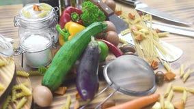 Voedselsamenstelling van verse groente, eieren en macaroni op houten achtergrond Ruw groente en ingrediënt voor het koken stock videobeelden