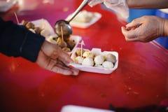 Voedselschenking: De handen van hongerig ontvangen voedsel van de provider stock foto