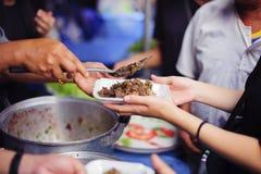 Voedselschenking: De handen van hongerig ontvangen voedsel van de provider royalty-vrije stock foto