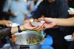 Voedselschenking: De handen van hongerig ontvangen voedsel van de provider royalty-vrije stock foto's