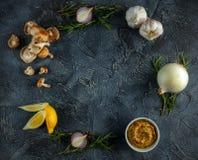 Voedselvoorbereidingen voor het koken, knoflook, ui, wilde paddestoelen, rozemarijn, citroen en gehele korrelmosterd op steenlijs Royalty-vrije Stock Fotografie