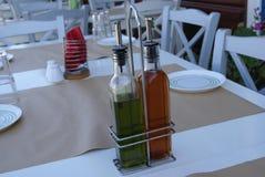 Voedselvulling van azijn en olijfolieflessen op een lijst royalty-vrije stock fotografie