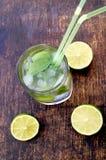 Voedzaam detoxwater met kalk en munt in een glas op de houten achtergrond Stock Foto
