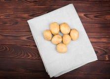 Voedzame, verse, organische nieuwe aardappels in een grijze stof op de donkere bruine houten lijst Ongekookte en smakelijke verse Stock Foto