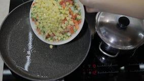 Voeg bevroren groenten aan een hete pan met olie toe erwten, graan, asperge, wortelen stock videobeelden