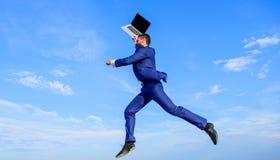 Voelt de zakenman geïnspireerde ondernemer het krachtige gaan wereld veranderen Geïnspireerde de mens houdt hierboven laptop terw royalty-vrije stock afbeeldingen