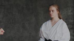 Voert de blonde vrouwelijke vechter in komono defensie en aanvalstactiek uit Gevechtsvaardigheden in origineel taekwondoklaslokaa stock video