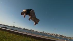 Voert de jonge mensen professionele acrobaat een tik die op een klip uit de rivier en cityscape overzien bij zonsondergang stock footage