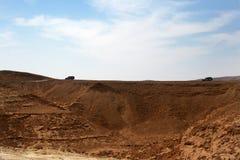 Voertuigen die in woestijn reizen Stock Foto's