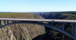 Voertuigen die zich op de brug tussen de bergen 4k bewegen