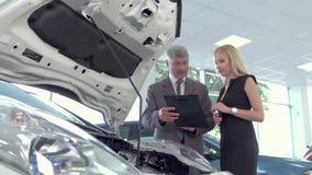 Voertuighandelaar die elektrische auto verkopen aan jonge mooie vrouw stock footage