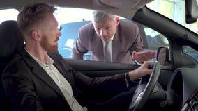 Voertuighandelaar die nieuwe auto tonen aan de jonge knappe mens stock video