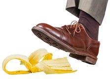 Voet in de linker bruine schoenmisstappen op een banaanschil Royalty-vrije Stock Foto's